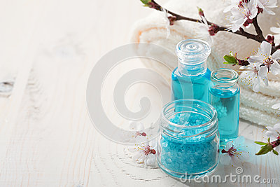 Mineral bath salts, shower gel, towels and flowers on the wooden table