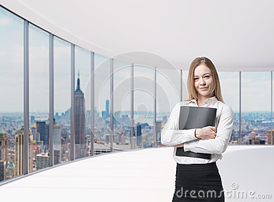 Business lady is holding a black document case. New York panoramic office. A concept of legal services.