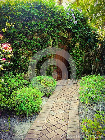 Cobble pathway to the secret gardens entrance of overhanging vines and a old rustic door