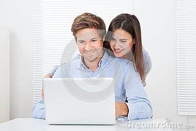 Surprised man looking at woman while using laptop