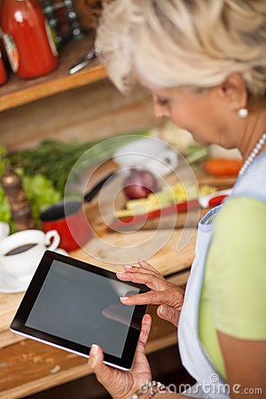 Senior woman using tablet in her kitchen