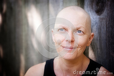 Balding cancer patient outside looking happy