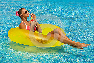 Sexy woman in bikini enjoying summer sun and tanning during holidays in pool with a cocktail