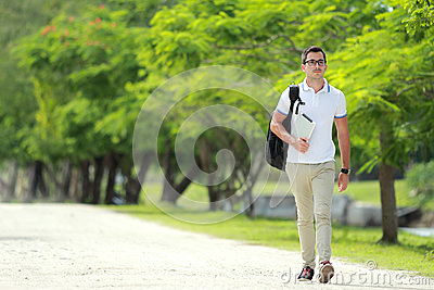 handsome college student walking by at college park with backpack and holding a tablet