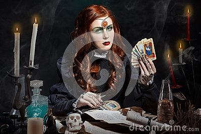 Beautiful girl with long hair mode in the image of the witch with the Tarot cards in his hands, black long false nails with bright