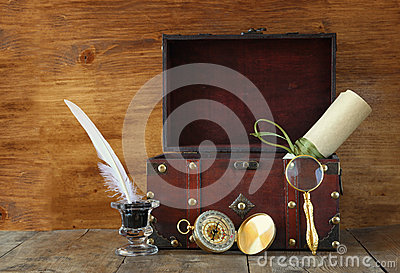 Antique compass, inlwell and old wooden chest on wooden table