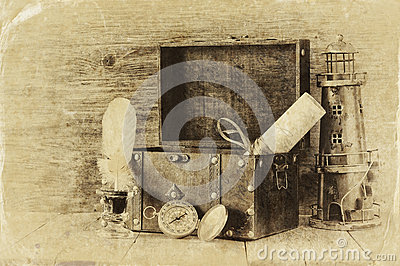 Antique compass, inkwell and old wooden chest on wooden table. black and white style old photo