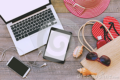 Laptop, digital tablet and smart phone with beach items over wooden background. View from above