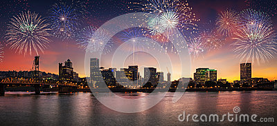 Flashing fireworks on a dramatic sunset sky with Portland, OR cityscape with Willamette river