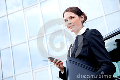 Young business lady outside with mobile phone