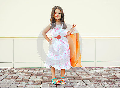 Portrait of beautiful little girl in dress with shopping bag