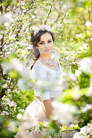 Portrait of beautiful girl posing outdoor with flowers of the cherry trees in blossom during a bright spring day
