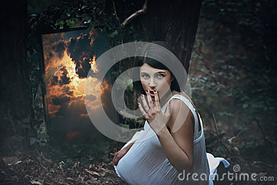 Magical mirror and surprised woman in dark forest