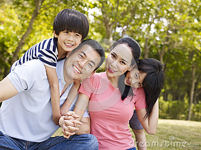 Outdoor portrait of happy asian family