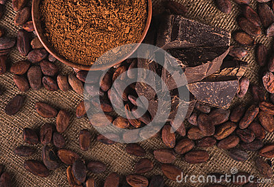 Raw cocoa beans, clay bowl  with cocoa powder, chocolate on sack