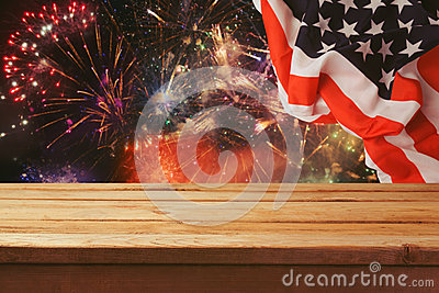 4th of July background. Wooden table over fireworks and USA flag. Independence day celebration