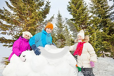 Group of happy kids build behind snow wall