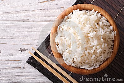 Steamed rice in a wooden bowl and chopsticks. horizontal top vie