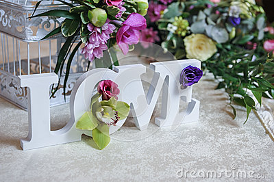 Wedding decor, LOVE letters and flowers on table. Fresh flowers and LOVE decoration on festive table. Luxurious wedding decoration
