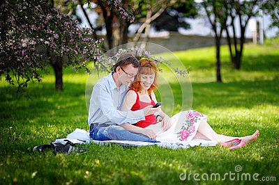 Young loving couple sitting at park on the grass in spring