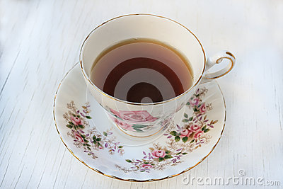 Cup of tea in a rose patterned china teacup and saucer