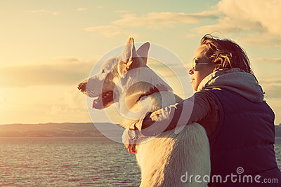 Young attractive girl with her pet dog at a beach