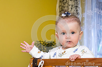 Little baby girl with bow on her head plays in the crib