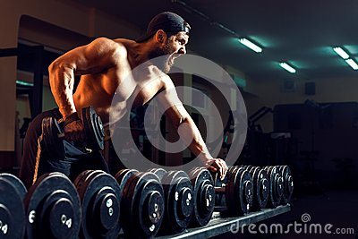 Muscular male bodybuilder working out in gym