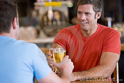 Two men toasting beer in a bar