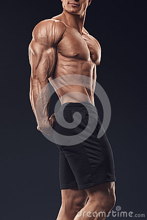 Strong and handsome young bodybuilder demonstrate his muscular t