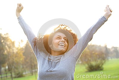 Cheerful young woman smiling with arms raised