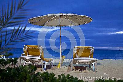 A parasol and two beach beds