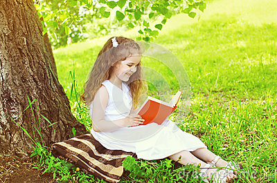 Smiling little girl child reading a book on the grass near tree