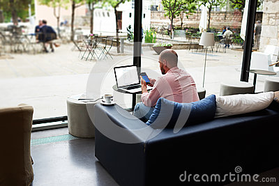 Modern business man busy working on smart phone and laptop computer