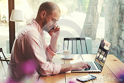 Business man talking on smart phone and look to laptop screen