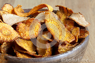 Detail of fried carrot and parsnip chips in rustic wood bowl.