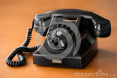 Old rotary dial phone on wooden desk