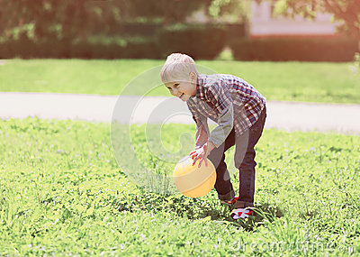 Little boy child playing with ball outdoors on the grass