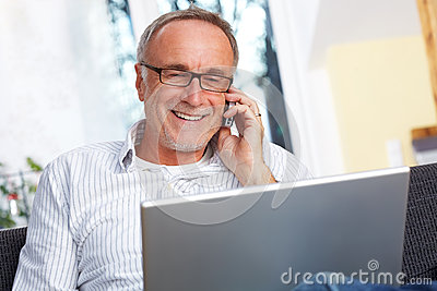 Mature man with laptop mobilephone and reading specs