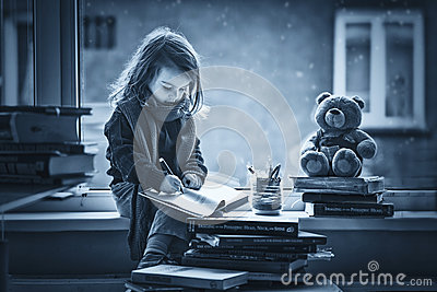 Adorable little girl, writing letter to Santa, sitting on a wind