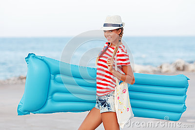 Beach woman happy and wearing beach hat with blue mattress having summer fun during travel holidays vacation