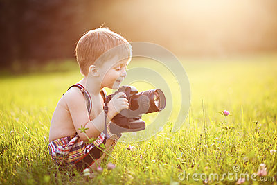 Smiling kid holding a DSLR camera in park