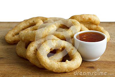 Heap of deep fried onion or calamari rings with chilli dip on wo
