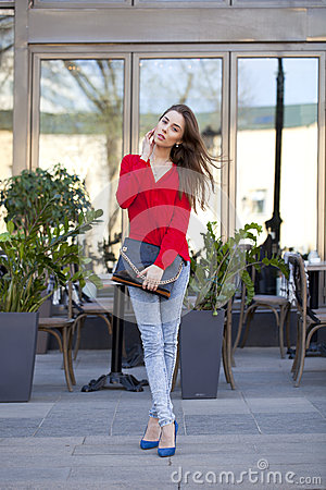 Young beautiful girl in blue jeans and red shirt on the backgrou