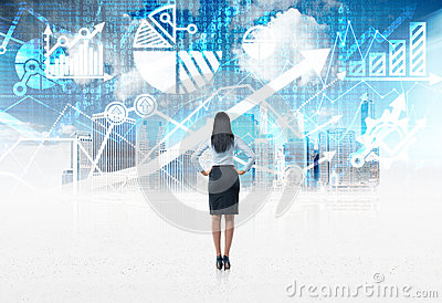 Rear view of the full-length of a business lady who stands in front of the blue digital financial charts background.