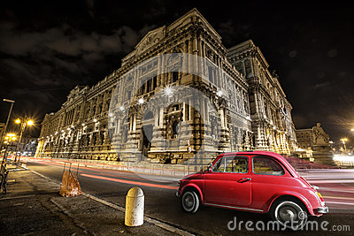 Old car Italian red by night. Italian historic monument