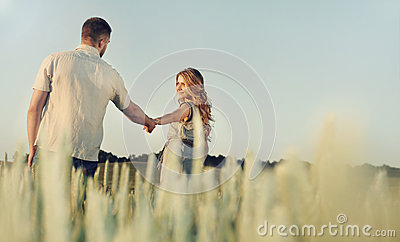 Stunning happy young couple in love posing in summer field holdi