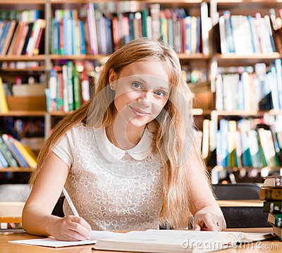 Portrait of a pretty female student studying in library with open book