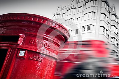 Traditional red mail letter box and red bus in motion in London, the UK.
