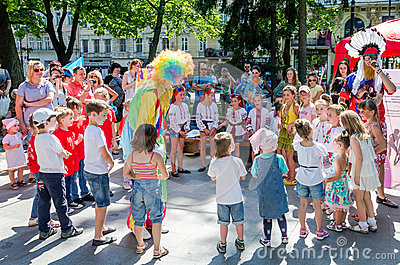 Lviv, Ukraine - July 2015: Yarych street Fest 2015. Clown and Indian play, sing and dance with the children in the park